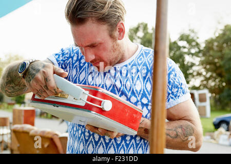 A man in a blue shirt with tattooed forearms, looking at a red vintage radio at a flea market. - Stock Photo