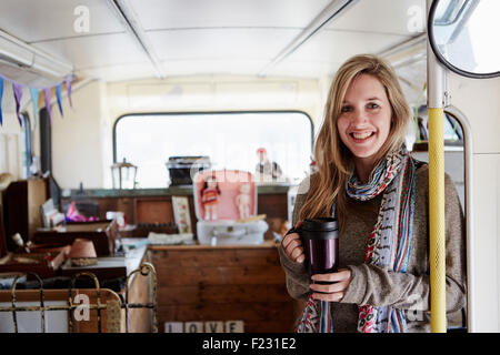 A woman standing in a bus converted into a vintage shop at a flea market surrounded by vintage objects. - Stock Photo