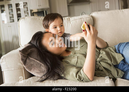 Woman lying on a sofa, smiling, cuddling with her young son and looking at a cell phone. - Stock Photo