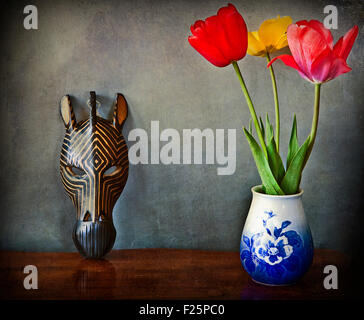 Vintage still life, three tulips in vase and wooden African mask - Stockfoto