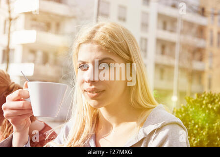 Portrait of a teenage girl drinking coffee, Munich, Bavaria, Germany - Stock Photo
