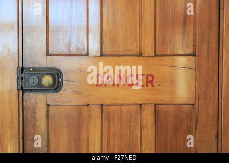 An old wooden closed door with red letters saying danger printed on it - Stockfoto