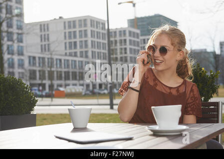 Young woman talking on a mobile phone at sidewalk cafe, Munich, Bavaria, Germany - Stock Photo