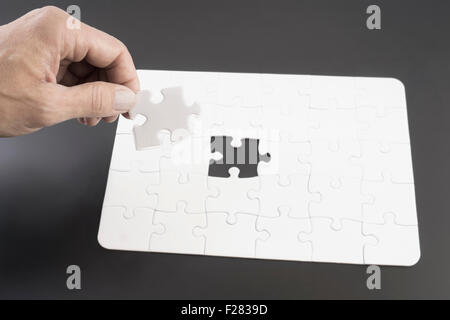 Hand placing last piece into jigsaw puzzle, Bavaria, Germany - Stock Photo