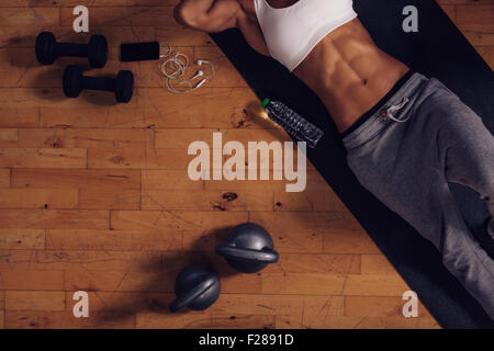 Top view of young woman lying on yoga mat in gym. Fitness woman relaxing after exercise session with a water bottle, - Stock Photo