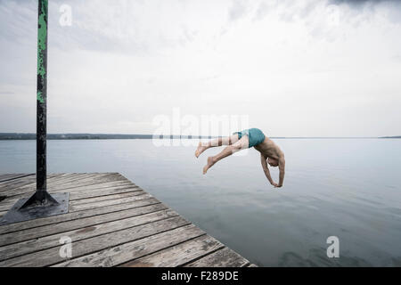 Mature man jumping into water on pier, Baden-Wurttemberg, Bavaria, Germany - Stock Photo
