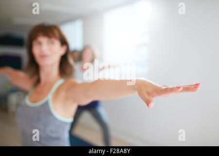 Woman stretching her arms at yoga class. Fitness trainer performing yoga in warrior pose. Virabhadrasana. Focus - Stock Photo