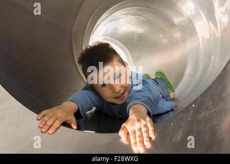 Boy sliding in a tunnel slide, Munich, Bavaria, Germany - Stock Photo