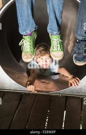 Boy sliding in a tunnel slide with two children dangling their feet, Munich, Bavaria, Germany - Stock Photo