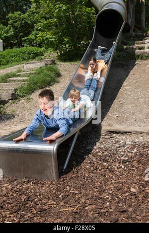 Three friends sliding down on tube slide in playground, Munich, Bavaria, Germany - Stock Photo