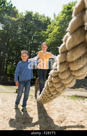 Boy and girl playing in playground, Munich, Bavaria, Germany - Stock Photo