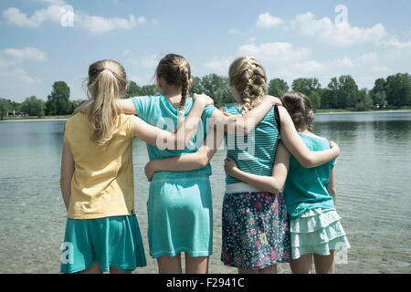 Group of friends standing in the lake, Bavaria, Germany - Stock Photo