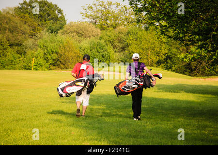 Two men carrying golf bags walk away across the course on a sunny, late spring afternoon in the golden light of - Stockfoto