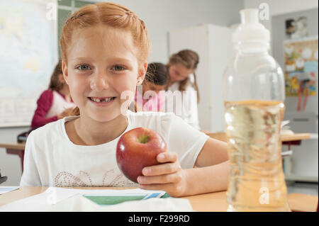 Portrait of a schoolgirl holding an apple in classroom, Munich, Bavaria, Germany - Stock Photo