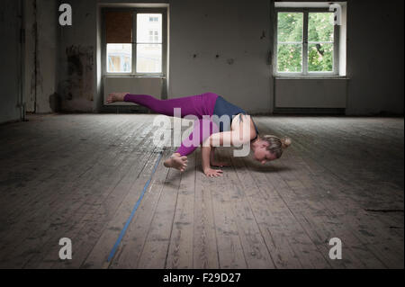 Mid adult woman practicing Eka pada koundinyasana I pose in Yoga Studio, Munich, Bavaria, Germany - Stock Photo