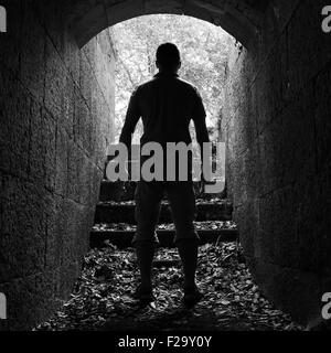 Young man stands in dark stone tunnel with glowing end, black and white square photo - Stock Photo