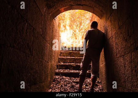Young man stands in dark stone tunnel with big fire in the end - Stock Photo