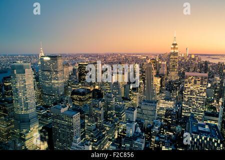 Beautiful New York City Manhattan buildings lit up at sunset - Stock Photo
