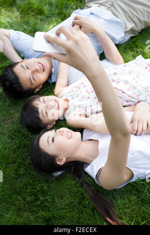 Happy young family lying on grass - Stock Photo