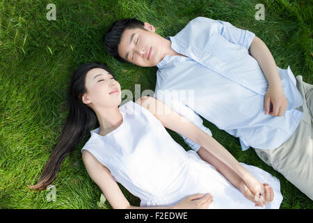 Happy young couple lying on grass - Stock Photo
