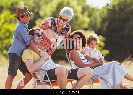 Multi-generation family relaxing in sunny field - Stock Photo