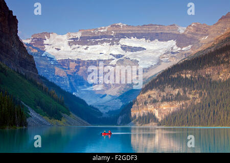 Tourists in red canoe on glacial Lake Louise with Victoria glacier, Banff National Park, Alberta, Canada - Stock Photo