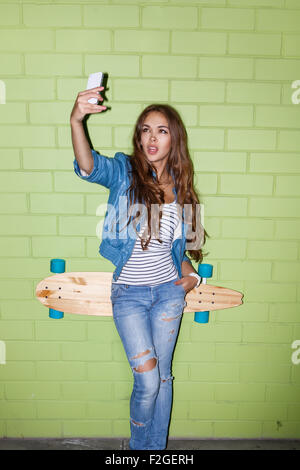 young beautiful long-haired brunette lady with wooden longboard skateboard taking selfie self portrait on her smartphone - Stock Photo