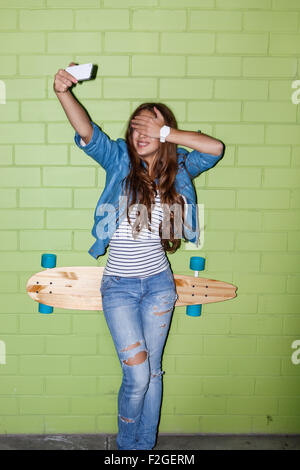 young beautiful long-haired brunette girl with wooden longboard skateboard taking a selfie self portrait of herself - Stock Photo