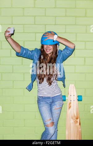 young beautiful long-haired brunette girl in blue helmet with wooden longboard skateboard taking a selfie self portrait - Stock Photo