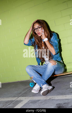 young beautiful long-haired brunette girl sits on her wooden longboard skateboard and touch her head while emotionally - Stock Photo
