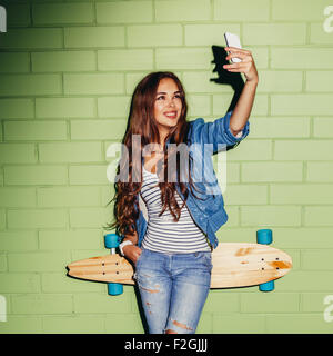 young beautiful long-haired brunette girl with wooden longboard skateboard making selfie self portrait on her smartphone - Stock Photo