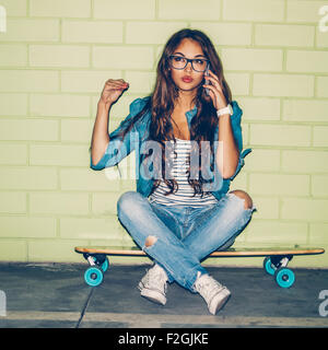 young beautiful long-haired brunette girl sits on her wooden longboard skateboard and do emotionally hand sign while - Stock Photo