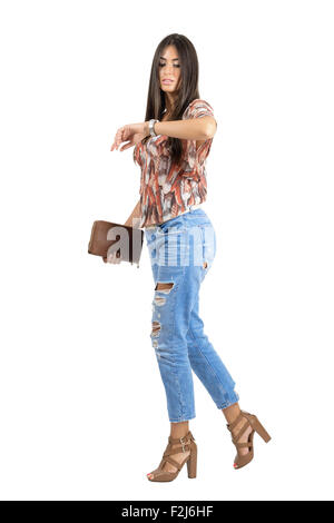 Side view of casual woman walking and checking time on hand watch. Full body length portrait isolated over white - Stock Photo