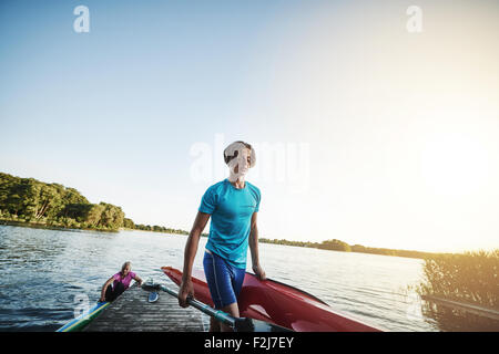 Young man carrying a kayak after getting out of the water - Stock Photo