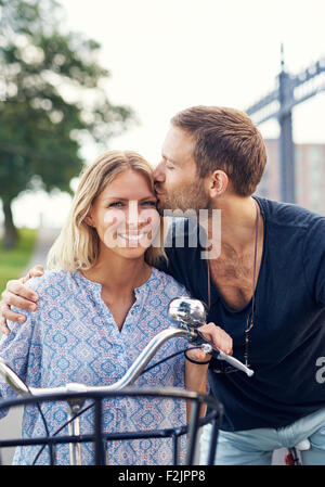 Affectionate young man kissing his girlfriend on the forehead as they enjoy a summer day in the fresh air on their - Stock Photo