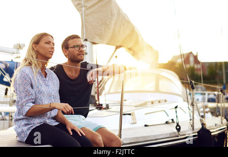 Sweet Young Lovers Sitting In Front of a Yacht and Looking Into the Distance During Sunset. - Stockfoto