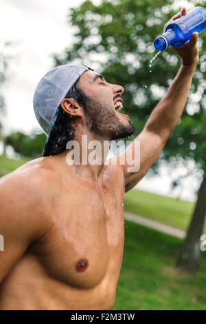 Athletic young man refreshing after training in the park - Stock Photo