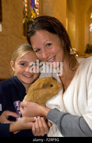 Mother and 10 year old daughter and their guinea pig at a church service where the congregation were invited to - Stock Photo
