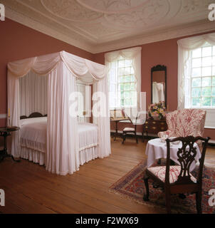 White drapes and linen on four poster bed in elegant Colonial style bedroom with wooden flooring - Stock Photo