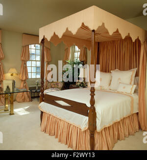 Peach pelmet and drapes on four poster bed in eighties bedroom - Stock Photo