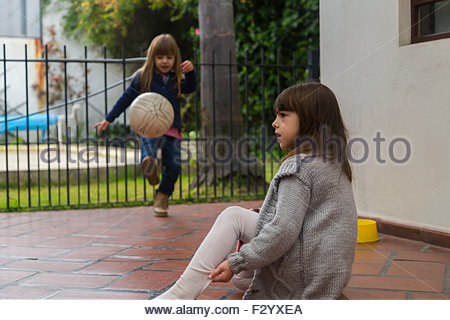 Two young kids playing football outdoors - Stock Photo
