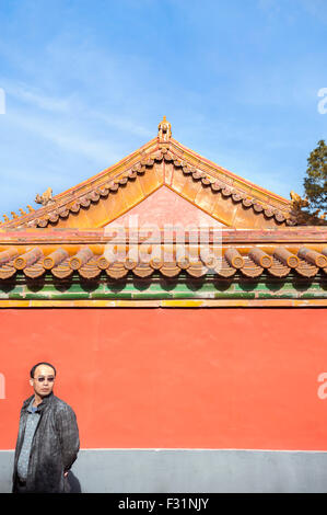 Chinese tourist stands in front of a red-painted wall at the Forbidden City, Beijing - Stockfoto