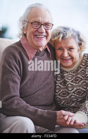 Happy elderly couple looking at camera and laughing - Stock Photo