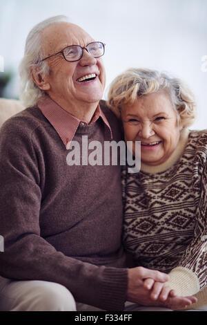 Joyful elderly man and woman in sweaters - Stock Photo