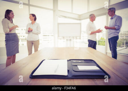 Planner in front of talking business people - Stock Photo