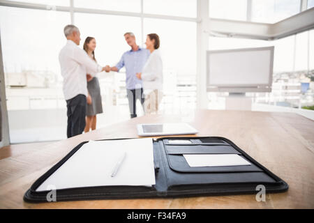 Planner in front of handshaking business people - Stock Photo