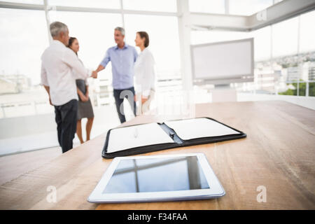 Tablet and planner in front of handshaking business people - Stock Photo