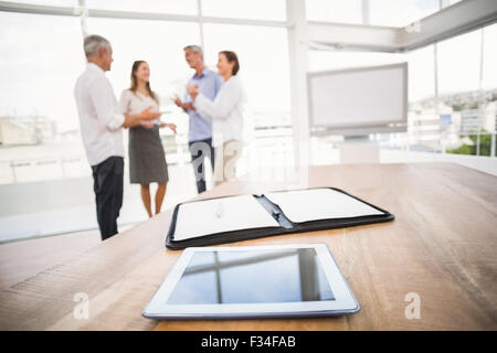 Tablet and planner in front of talking business people - Stock Photo