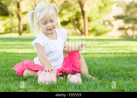 Cute Little Girl Having Fun with Her Large and Small Piggy Banks Outside on the Grass. - Stockfoto