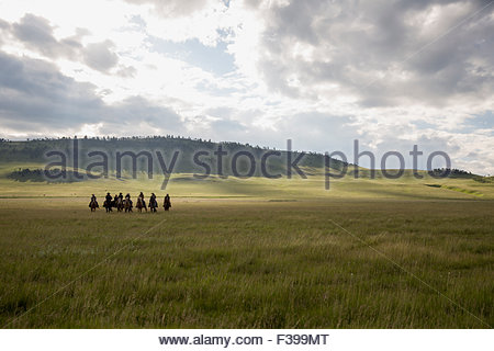 Female ranchers horseback riding in remote field - Stock Photo